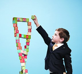 A child builds a tower resembling the structure of DNA with blocks.